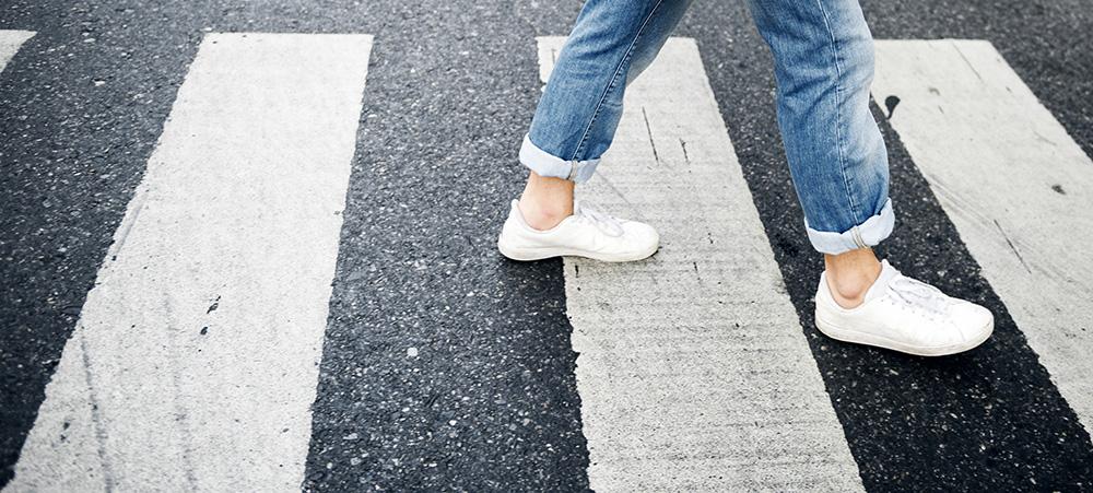 Person walking across the pedestrian lane