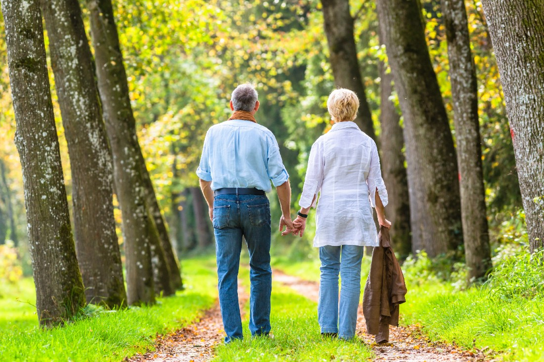 elderly couple walking on a grassy path in the woods